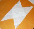 Kapesníček úhlopříčně přestřihneme a získané trojúhelníky přeložíme přes sebe